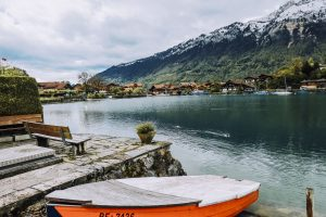 small boat sitting on the shore of Lake Brienz